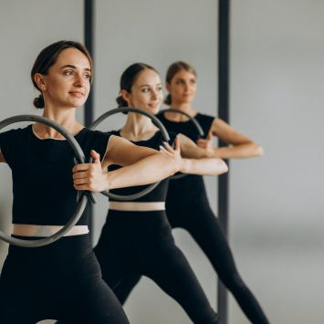 group-pilates-instructors-exercising-reformers